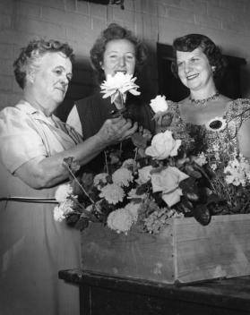 Chairwomen of local garden clubs at the Flower Show admire a flower arrangement