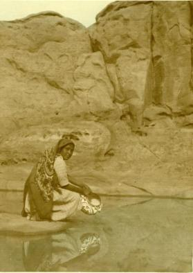 An Acoma woman kneels next to a stream, holding a pot