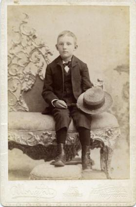 Portrait of unidentified young boy seated on a sofa