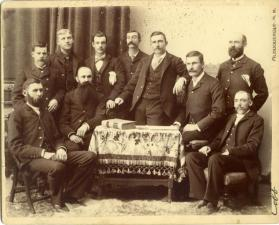 Portrait of ten men gathered around a large book on a table